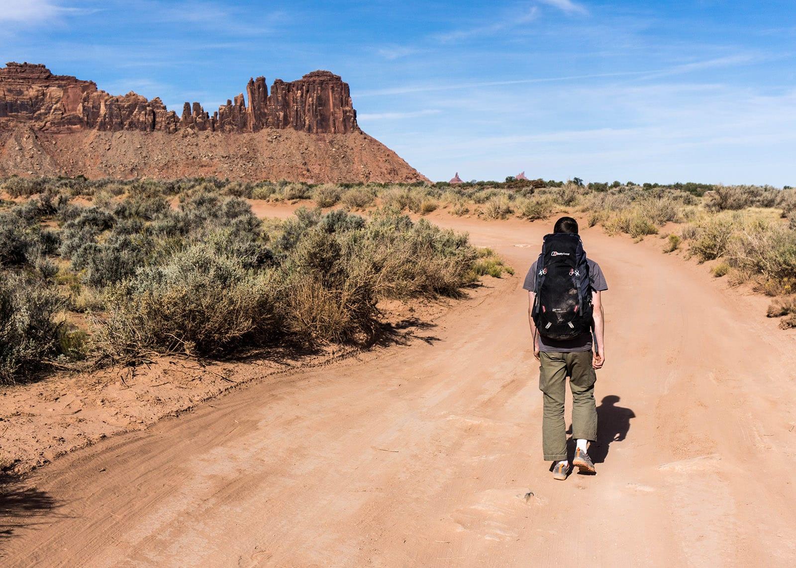 PÅ VEI: En anmarsj kan gi ro i sinnet. Og det kan man behøve av og til. Her er Tellef på vei mot en ny dag, og kan skimte Reservioar Wall i det fjerne. Turen gikk imidlertid ikke dit denne dagen. Så lange anmarsjer er det ikke i Indian Creek. Foto: Kristian Sletten Hanisch