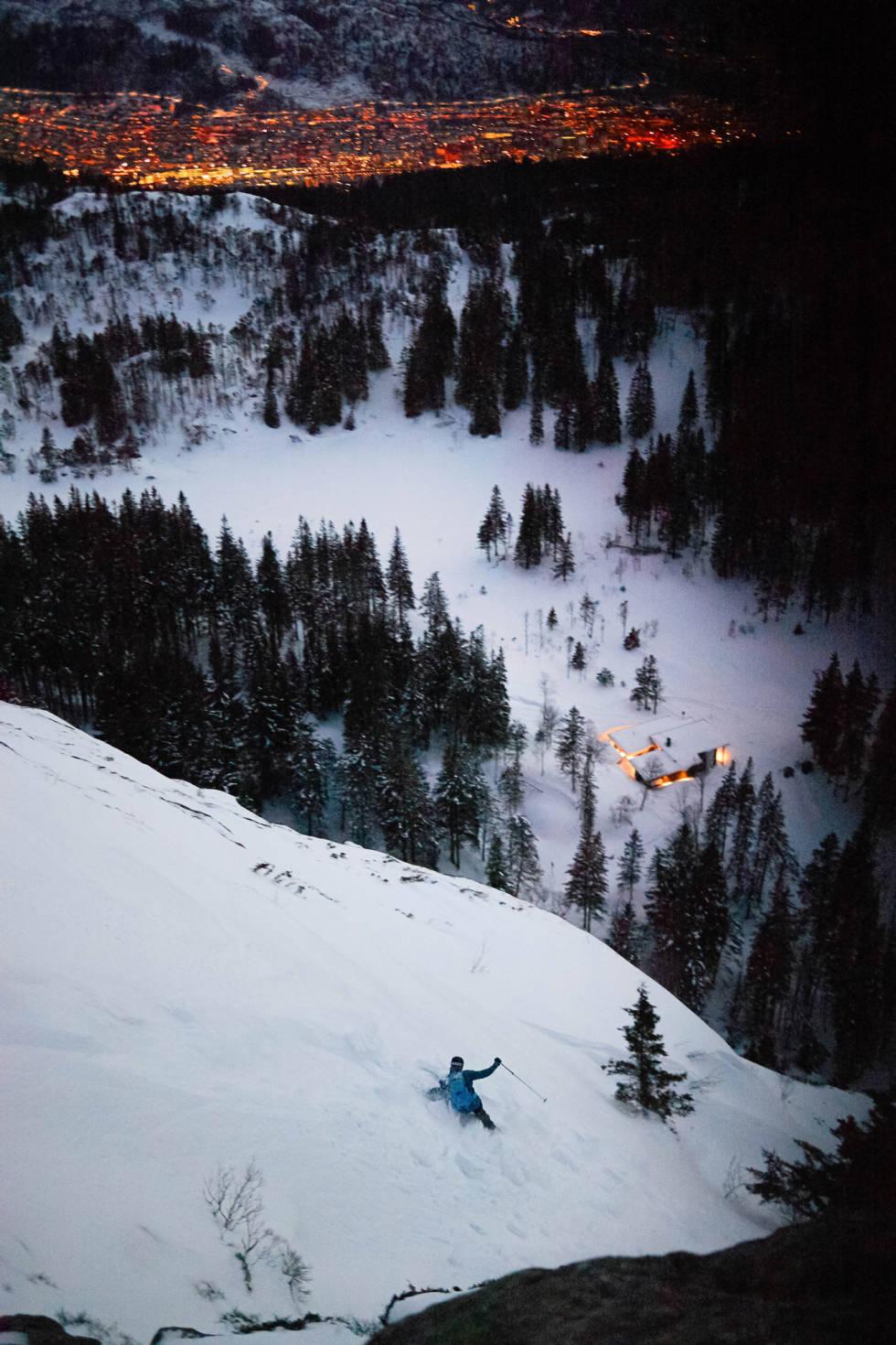 BLÅTIMEN: Fra toppen av Blåmanen legger det seg en sjelden gang snø i en tynn stripe rett ned til Brushytten. I vinter skjedde det. Og i vinter raste all snøen ut i et svært snøskred, slik at bergenspolitiet stengte turstien som ligger ved foten av fjellet. Etter en stund satte snøen seg, og vi fikk mer påfyll. Asbjørn Hellås kjenner sin besøkelsestid, og legger en sving ned mot langrennsløypa like før dagen er slutt. Vel nede kan han stake seg mellom lycrakledde langrennsløpere og rett hjem til huset i Sandviken. Foto: Alric Ljunghager