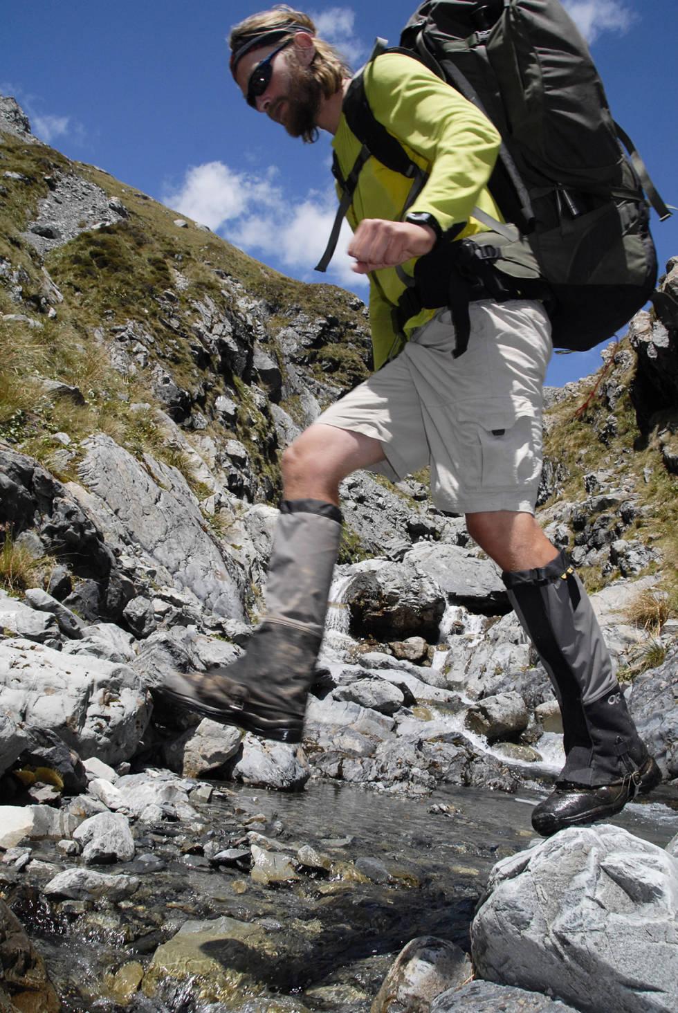 Mann går i fjellet med tunge fjellsko