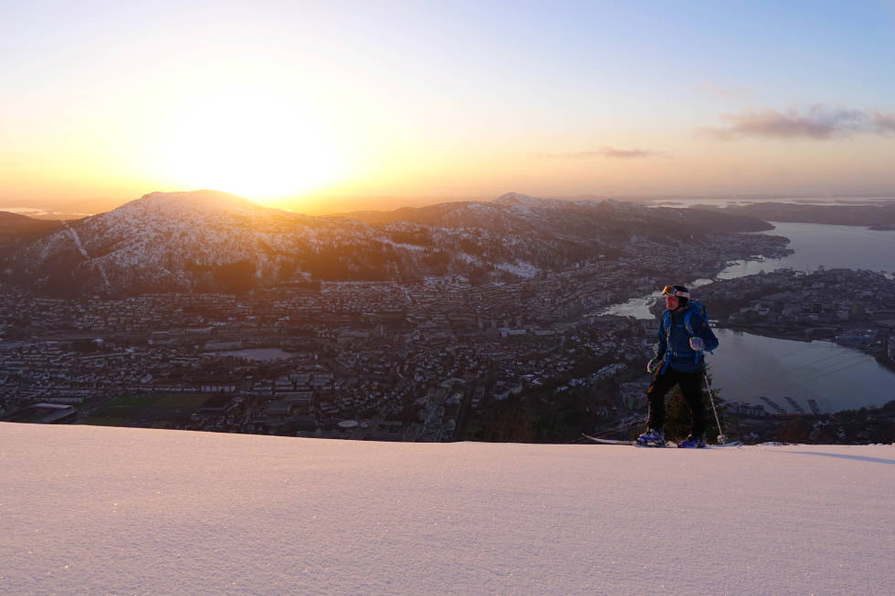 HJEMMEBANE: Vinteren i Bergen balanserer på kanten av nullpunktet. Det er ingen tvil om at det kommer nok nedbør på denne siden av fjellet, men den har dessverre en lei tendens til å falle som regn heller enn snø – også om vinteren. Men det er små marginer, og i år falt nedbøren stort sett på riktig side av nullpunktet. I tillegg fikk vi en lang periode med høytrykk og kulde, som gjorde det mulig å leike seg i byfjellene i flere uker. Slik som Asbjørn gjør her, som får seg tid til en ettermiddagsøkt på Ulriken etter arbeidsdagen er over. I bakgrunnen er sola på vei ned i havet. Spørs om man får denne utsikten på bynær skitur på andre siden av fjellet. Foto: Henning S. Skjetne