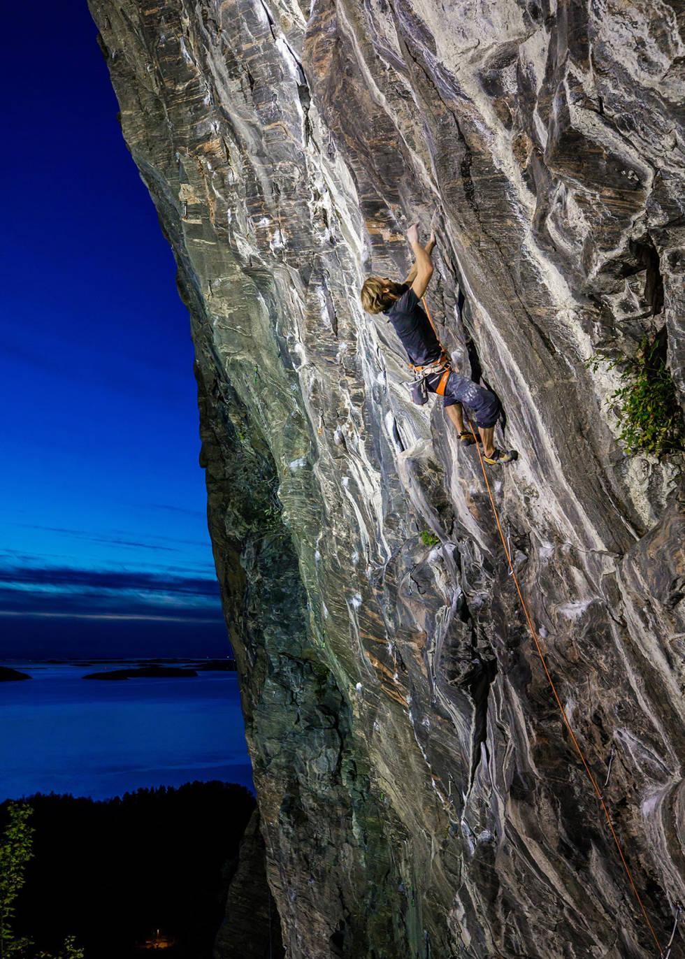 HARDT: Håvard Jendem klatrer Blodig Alvor (9) i flombelysning. Foto: Terje Aamodt