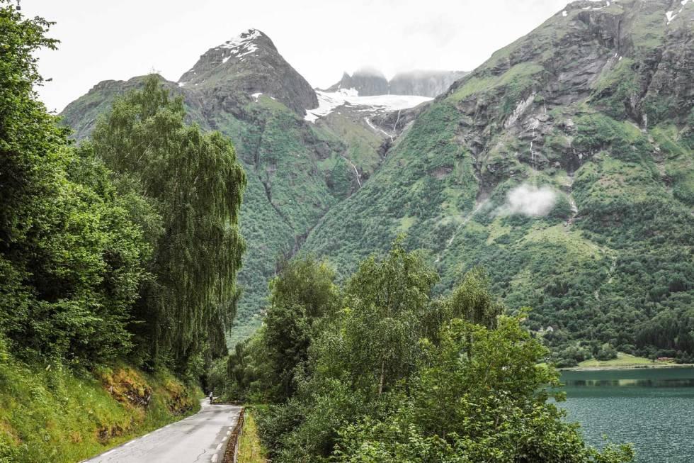FRODIG: Den hvitstiplede veien forbi Hjelle er en verdig avslutning på turen over fjellet. Hovedveien går i tunell, den gamle veien i en slynge langs Opstrynsvatnet.
