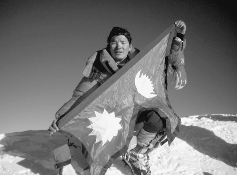 Da Chhiring nådde toppen av K2, brettet han ut det nepalske flagget for å feire. Han nådde toppen klokka 18.37, for sent til å unngå å klatre ned i kveldsmørket og kulden. Foto: Pemba Gyalje Sherpa