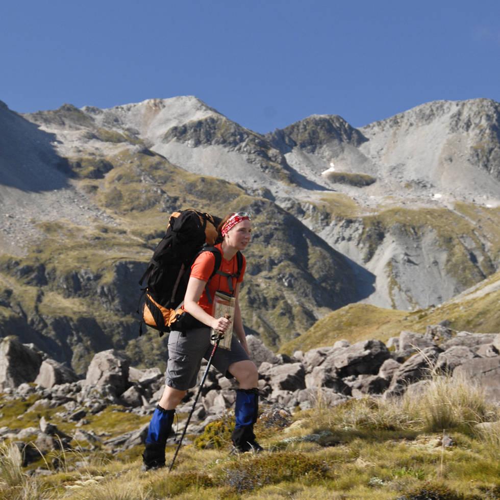 Kvinne bærer ryggsekk i fjellet